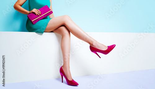 Fotografiet Beautiful legs woman wearing blue dress with a purple purse hand bag with red high heels shoes sitting on the white bench