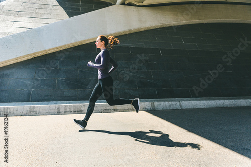 Canvas Print Woman jogging or running, side view with shadow