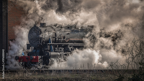 Obraz na plátně A steam train locomotive emerges from the mist, steam and smoke taken in a lands