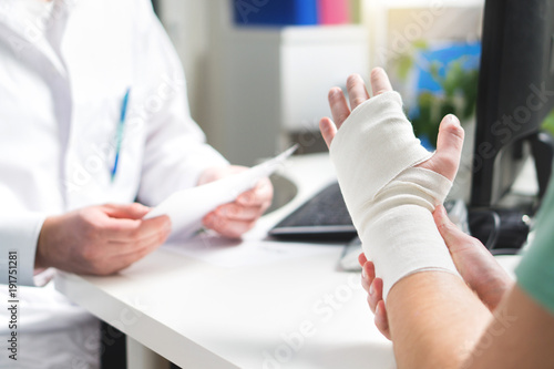 Fototapeta Injured patient showing doctor broken wrist and arm with bandage in hospital office or emergency room