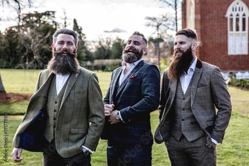 Tablou Canvas Smart Men with beard and moustache wearing a suit near a castle