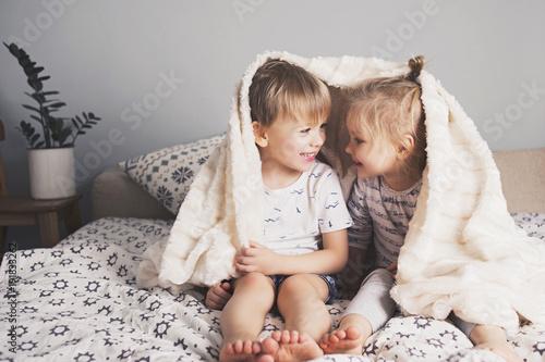 Two pretty kids embrace under blanket
