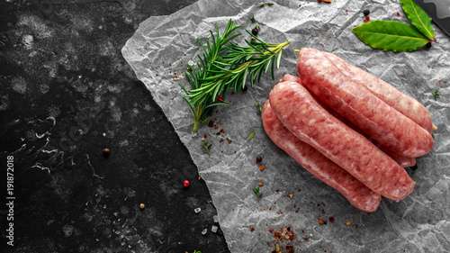 Fotografia Freshly made raw breed butchers sausages in skins with herbs on crumpled paper