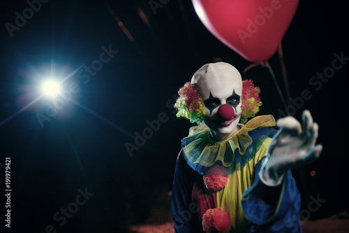 Fotografering Image of clown with red balloon on background of burning lantern