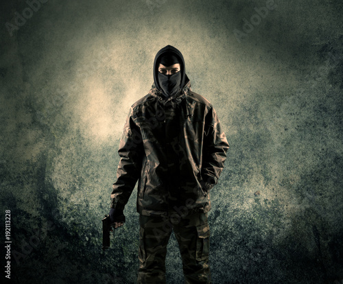 Fotografia Portrait of a heavily armed masked soldier with grungy background
