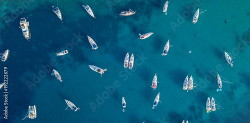 Aerial view of many anchoring yacht in open water.