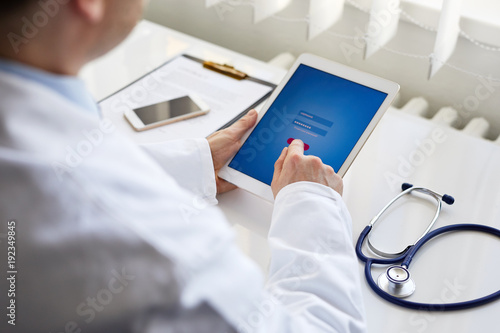 Male doctor presses on screen digital tablet