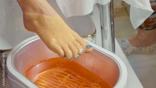 Photo Wax bath for feet at beauty spa salon, close-up.