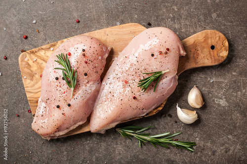 Fresh chicken fillet with spices on cutting board