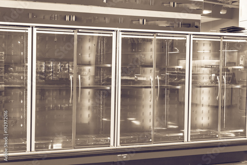 Empty commercial fridges at grocery store in America. Sold out frozen food section. Vintage tone