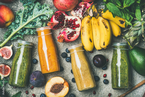 Flat-lay of colorful smoothies in bottles with fresh tropical fruit and vegetables on concrete background, top view. Healthy, clean eating, vegan, vegetarian, detox, dieting breakfast food concept