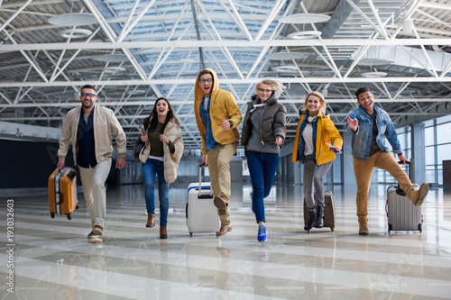 Full length portrait of group of tourist chasing each other at the airport. Their faces are joyous