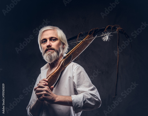 Canvas Print Studio portrait of a smiling handsome old man with a gray beard and white shirt holding a crossbow on shoulder