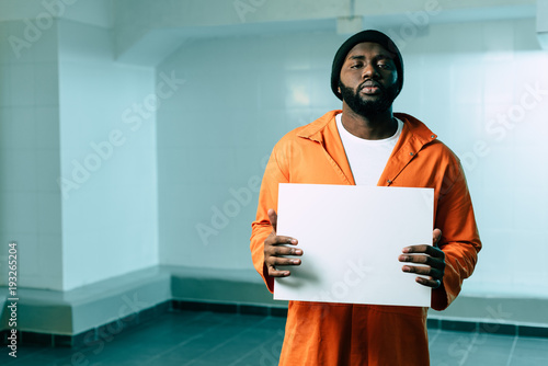 african american prisoner holding blank placard and looking at camera Fototapet
