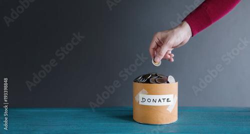 Billede på lærred Donation Concept. Hand putting Money Coin into a Donate Box