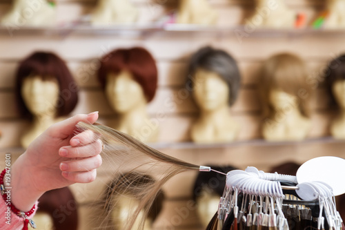 girl in her hand chooses a hair color wig of a natural blond Fototapeta