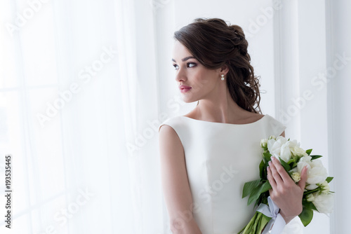 Obraz na płótnie beautiful bride holding wedding bouquet and looking at window