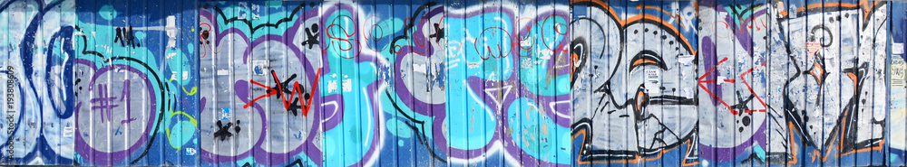 The old wall, painted in color graffiti drawing blue aerosol paints. Background image on the theme of drawing graffiti and street art