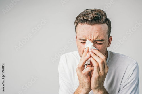 Foto Close up of guy in white t-shirt sneezing to handkerchief and wiggling at the samte time