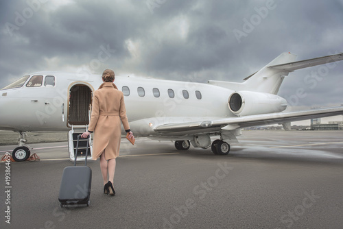 Fotografie, Obraz Full length female keeping baggage while going to private jet