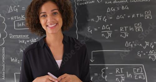 Portrait of black teacher giving math lesson on chalkboard