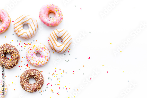 Donuts decorated icing and sprinkles on white background top view copy space pat фототапет