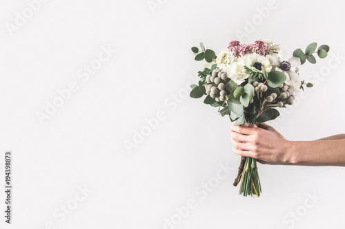 Foto cropped shot of woman holding beautiful bridal bouquet isolated on grey