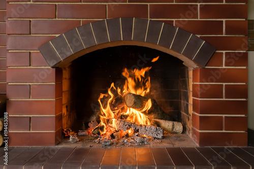 Stampa su Tela A brick fireplace in which a fire burns