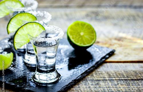 Obraz na plátně Bar set with shots, fresh lime and salt on wooden background