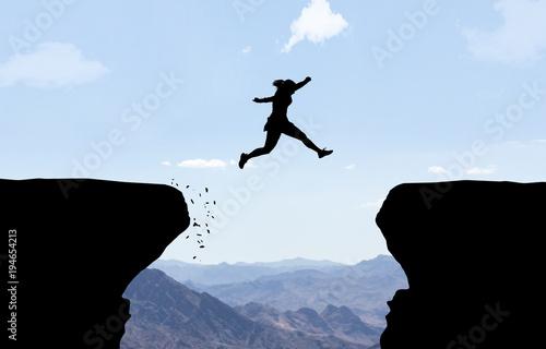 Fotografiet Frau springt über Abgrund.