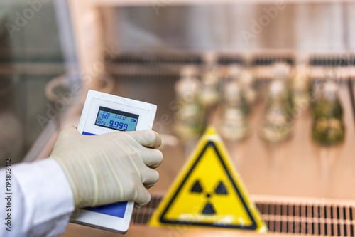 Fotografia the scientist keeps a dosimeter in his hand to measure the level of radioactive