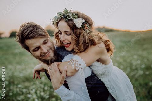 Fotografia, Obraz Beautiful bride and groom at sunset in green nature.