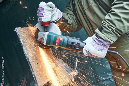 Obraz na plátne worker grinding cutting metal sheet with grinder machine and sparks