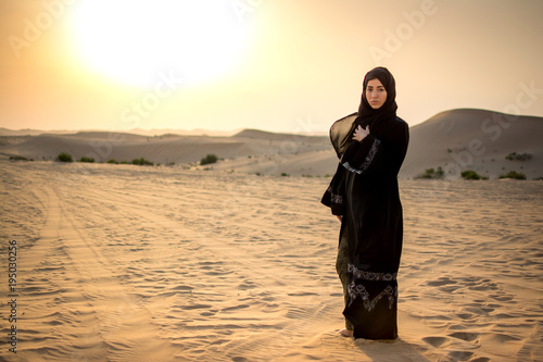 Arab woman standing in the desert during sunset.