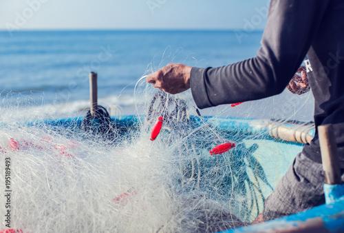 fisherman on boat with net in hands Fototapeta