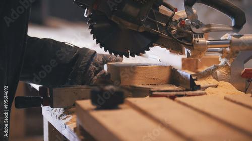 Billede på lærred Worker carpenter figuring wooden board before circular saw sawing