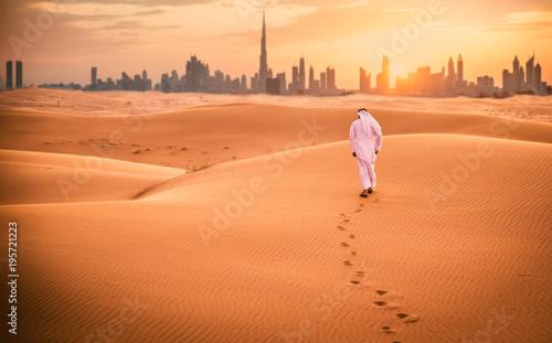 Fototapeta premium Arabski mężczyzna chodzący po pustyni w tradycyjnych emiratach