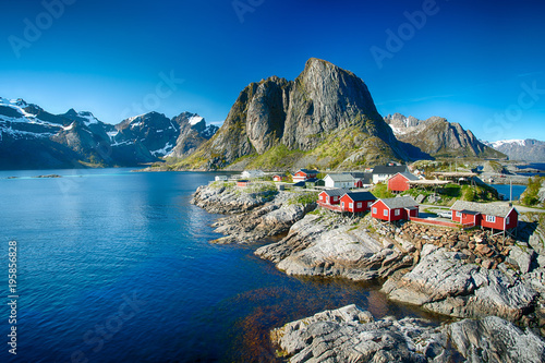 Stampa su Tela The village of Reine under a sunny, blue sky, with the typical red rorbu houses