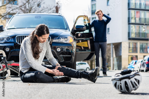 Full length of a young female bicyclist fallen down on street with serious injuries after traffic accident with the 4x4 car of a young man