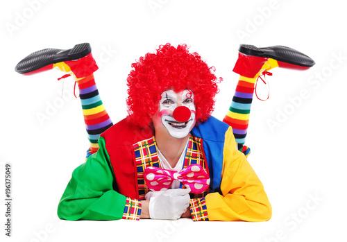 Foto Glücklicher Clown getrennt über dem weißen Hintergrund, der auf den Fußboden leg