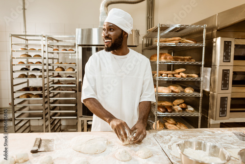 Tableau sur Toile african american baker preparing raw dough for pastry on baking manufacture