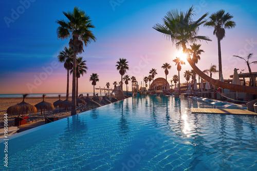 Fototapeta Resort pool in a beach with palm trees sunrise