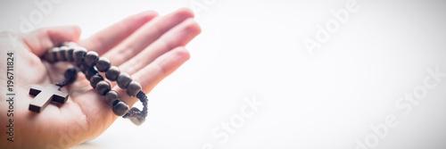 Fototapeta Hand holding rosary beads