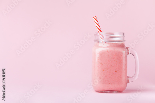 Strawberry smoothie or milkshake in mason jar on pink pastel background. Healthy food for breakfast and snack.
