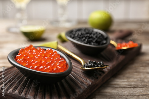 Bowls with black and red caviar on table