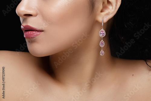 Obraz na płótnie Long earring with violet precious stones hang from woman's ear