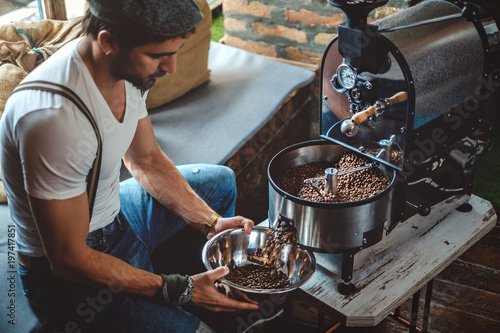 Hipster catching roasted coffee from the roaster with a dish Fototapeta
