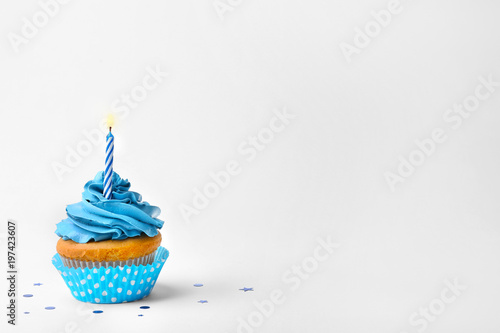 Birthday cupcake with candle on white background