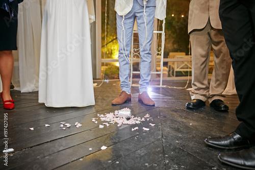 Photo groom at jewish wedding steps on a glass