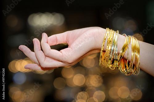 Obraz na plátne Beautiful woman hand hold gold bracelet jewelry, accessory and fashion